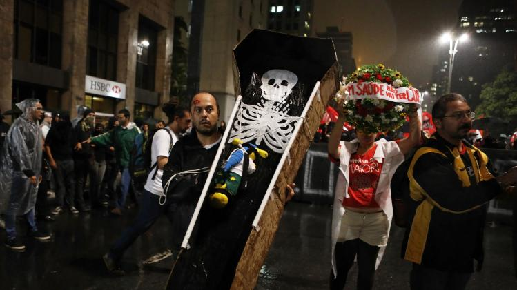 A demonstrator holds up a coffin containing a fake skeleton and the official mascot of the FIFA 2014 World Cup, Fuleco the Armadillo, during a protest in Sao Paulo