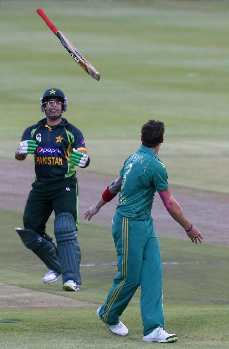 Pakistan's Umar Akmal laughs as South Africa's Dale Steyn returns his bat during their second Twenty20 cricket match in Cape Town