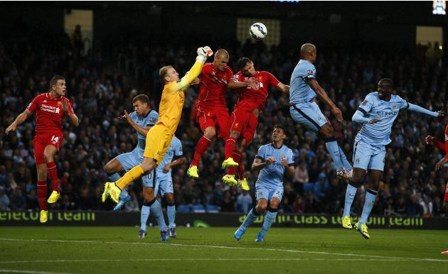 Manchester City's goalkeeper Hart punches the ball away from Liverpool's Skrtel and Lovren during their English Premier League soccer match at the Etihad stadium in Manchester