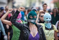 Supporters of the Russian punk band 'Pussy Riot' wear masks and tape their mouths shut as they protest in front of the Russian embassy in Warsaw on August 17, 2012. Moscow police made several arrests on Friday as dozens of activists staged a picket outside the headquarters of the Russian prison service on women's day to call for the punk rock group's release
