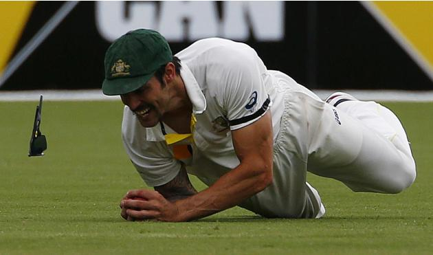 The sunglasses of Australia's Johnson falls off as he dives to take a catch to dismiss England's Ian Bell during the fourth day of the second Ashes test cricket match in Adelaide
