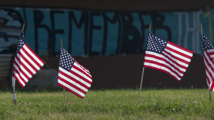 Four of 19 United States flags are planted in the grass outside Prescott High School with a banner to honor 19 fallen Granite Mountain Hotshot firefighters on display on a nearby wall, Friday, July 5, 2013 in Prescott, Ariz. Nearly a week after 19 Granite Mountain Hotshot firefighters died battling a blaze near Yarnell, Ariz., small memorials continue to pop up around the town. (AP Photo/Julie Jacobson)
