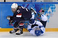 Hilary Knight (left) of the US clashes with Finland's Minnamari Tuominen during a Women's Ice Hockey Group A match at the Shayba Arena during the Sochi Winter Olympics on February 8, 2014