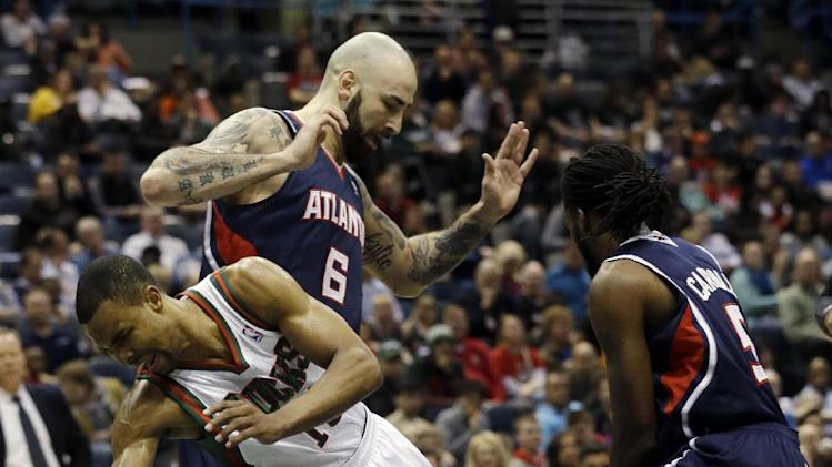 Milwaukee Bucks' Ramon Sessions, front left, loses the ball as he drives between Atlanta Hawks' Pero Antic (6) and DeMarre Carroll (5) during the second half of an NBA basketball game on Wednesday, April 16, 2014, in Milwaukee