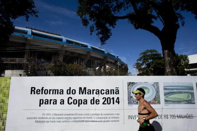 "ADVANCE FOR USE WEEKEND OF DEC. 31-JAN 1 AND THEREAFTER- FILE - In this Dec. 21, 2011, file photo, a man runs by a sign that reads in Portuguese ""Reform of Maracana for the 2014 World Cup"" outside Mar"
