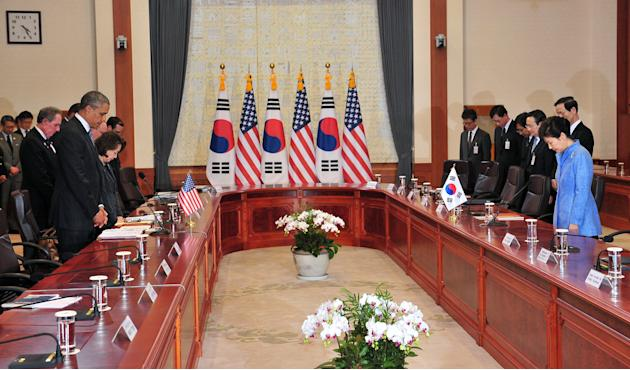 U.S. President Barack Obama, left foreground, and South Korean President Park Geun-hye, right, pay a silent tribute for victims of South Korea's sunken ferry Sewol during their meeting at the pres
