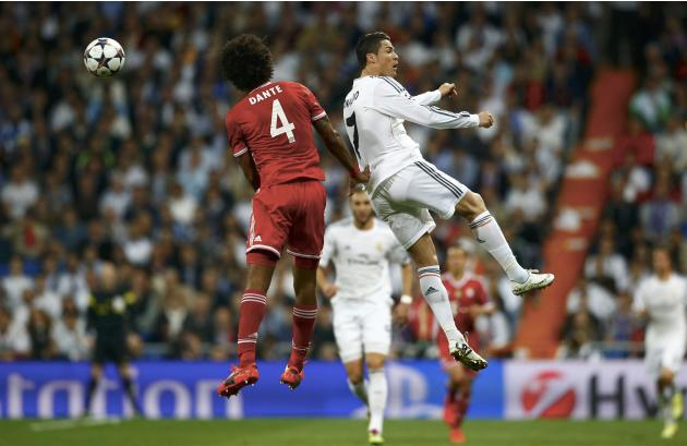 Bayern Munich's Dante and Real Madrid's Ronaldo jump for a high ball during their Champions League semi-final first leg soccer match at Santiago Bernabeu stadium in Madrid