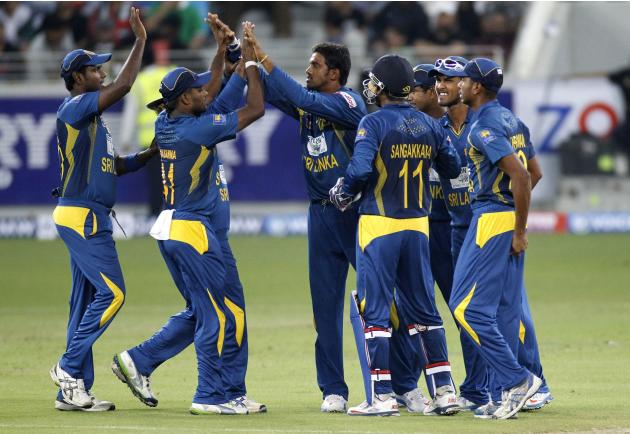 Sri Lanka's Sachithra Senanayake celebrates with his team mates the wicket of Pakistan's Ahmed Shahzad during their second Twenty20 international cricket match in Dubai