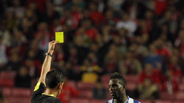 Porto's Silvestre Varela, right, is shown a yellow card by referee Pedro Proenca during a Portugal Cup semifinal second leg soccer match between Benfica and Porto at Benfica's Luz stadium in Lisbon, Wednesday, April 16, 2014. Benfica won 3-2 on aggregate and will play the final