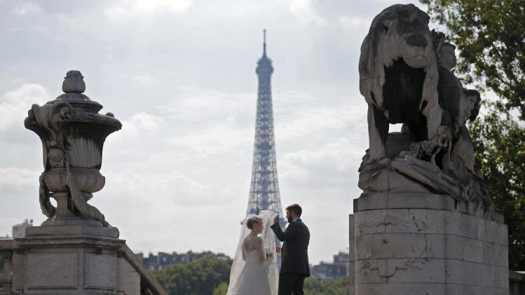 A wedding couple pose for their own photographer on the Alexandre III bridge in Paris