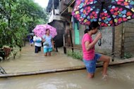 People wade through floodwaters in Quezon City Suburban Manila on August 6, 2012. Residents of low-lying slums fled the huge shantytowns lining Manila's rivers and sewers for the safety of schools, gymnasiums and government buildings, the civil defence office said