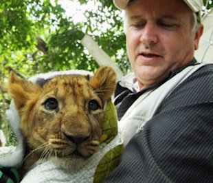 Tim Phillips with a lion cub in a scene from the 'Lion Ark' documentary.