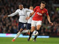 Manchester United's midfielder Michael Carrick (R) fights for the ball with Tottenham's striker Jermain Defoe during their English Premier League football match at Old Trafford in Manchester. Tottenham won 3-2