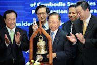 Cambodian Minister of Economy and Finance Keat Chhon (C) rings a bell during the launching ceremony at the Cambodian Securities Exchange (CSX) in Phnom Penh on April 18, 2012. The CSX finally began trading shares, nine months after it officially opened, when a water monopoly became the first firm to list