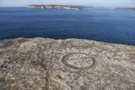 Inscriptions carved near the edge of a cliff with Sydney's skyline in the distance.
