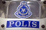 Photo illutration shows a Malaysian Police logo on a motorbike in downtown Kuala Lumpur. An Australian woman and a Nigerian man have been arrested in Malaysia after drugs were discovered in the car they were driving in the capital Kuala Lumpur, police said Saturday