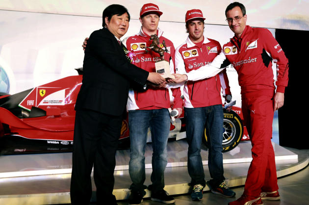 CORRECTS THE NAME AND TITLE OF FERRARI REPRESENTATIVE - Tan Xuguang, left, chairman of Weichai Power, shakes hands with Ferrari Sponsorship Management head Michele Pignatti, right, as drivers, Kimi Ra