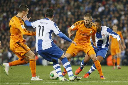 Real Madrid's Cristiano Ronaldo and Karim Benzema battle for the balll against Espanyol's Joan Capdevila and Sidnei Rechel during their King's Cup soccer match at Cornella El Prat stadium, in Barcelona