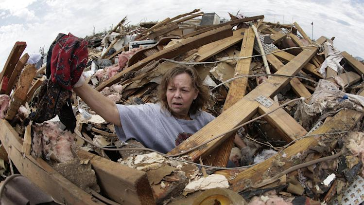 Carol Kawaykla salvages items at her tornado-ravaged home Thursday, May 23, 2013, in Moore, Okla. Cleanup continues three days after a huge tornado roared through the Oklahoma City suburb, flattening a wide swath of homes and businesses. (AP Photo/Charlie Riedel)