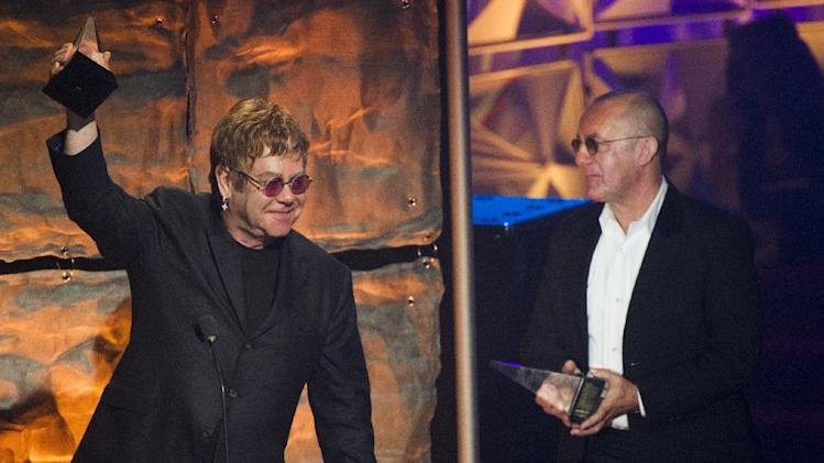 "Elton John, left, and Bernie Taupin accept the ""Johnny Mercer"" award at the Songwriters Hall of Fame 44th annual induction and awards gala on Thursday, June 13, 2013 in New York. (Photo by Charles Sykes/Invision/AP)"