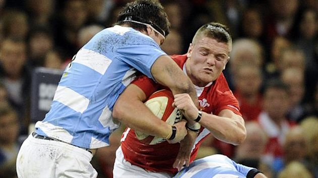 Wales' Leigh Halfpenny (C) is tackled by Argentina's Manuel Carizza