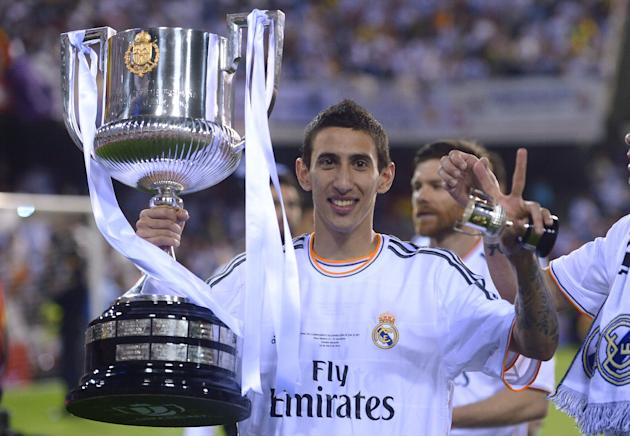 Real's Angel Di Maria poses with the trophy at the end of the final of the Copa del Rey between FC Barcelona and Real Madrid at the Mestalla stadium in Valencia, Spain, Wednesday, April 16, 2014.