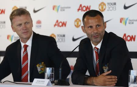 File photo of Manchester United player Giggs talking while manager Moyes looks at him during a news conference in central Sydney