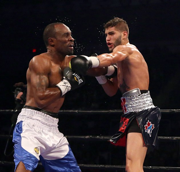 Prichard Colon, right, punches Vivian Harris during their WBC welterweight boxing match Friday, Sept. 11, 2015, in Toronto. (Peter Power/The Canadian Press via AP) MANDATORY CREDIT