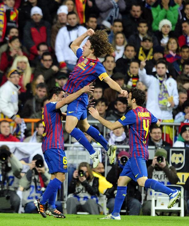 Barcelona's Captain Carles Puyol (C) Celebrates With Barcelona's Midfielder Cesc Fabregas (R) And Barcelona's AFP/Getty Images