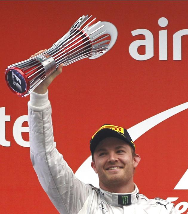 Mercedes Formula One driver Rosberg celebrates with his trophy after placing second in the Indian F1 Grand Prix at the Buddh International Circuit in Greater Noida