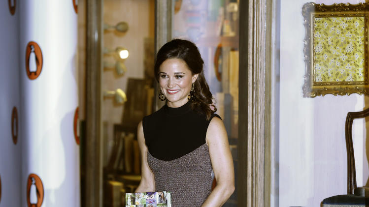 "Pippa Middleton, sister to the Duchess of Cambridge, formerly known as Kate Middleton, poses for the media as she arrives at a bookshop to promote her new book ""Celebrate: A Year of British festivities for families and friends"", in London Thursday, Oct. 25, 2012. (AP Photo/Kirsty Wigglesworth)"