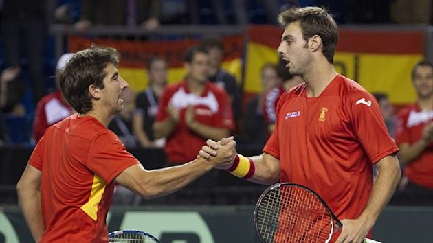Spain's Marcel Granollers (R) and Marc Lopez celebrate their teams match win against Canada's Daniel Nestor and Vasek Pospisil during their doubles match on the second round of the Davis Cup