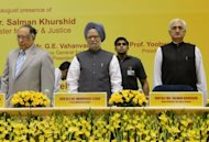 Indian Prime Minister Manmohan Singh (C), flanked by Indian Chief Justice S.H. Kapadia (L) and Union Minister for Law and Justice Salman Khurshid (R), attends a legal conference in New Delhi.