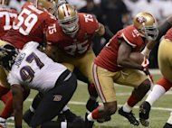 Frank Gore (R) of the San Francisco 49ers carries the ball against the Baltimore Ravens during Super Bowl XLVII on February 3, 2013 in New Orleans, Louisiana. The Ravens won 34-31