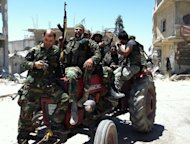 Syrian soldiers sit on a tractor on June 5, 2013 in the city of Qusayr in Syria's central Homs province. The United States condemned an assault by Syrian troops on the town of Qusayr, claiming the regime had relied on Hezbollah to win the battle and caused tremendous suffering