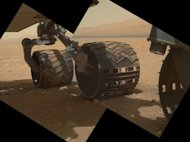 This view of the three left wheels of NASA's Mars rover Curiosity combines two images that were taken by the rover's Mars Hand Lens Imager (MAHLI) during the 34th Martian day, or sol, of Curiosity's work on Mars (Sept. 9, 2012). In the distance