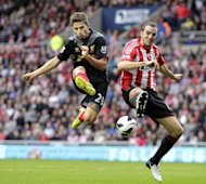 Sunderland's defender John O'Shea (R) clashes with Liverpool's striker Fabio Borini during the English Premier League football match at The Stadium of Light in Sunderland, north-east England. The match ended in a 1-1 draw