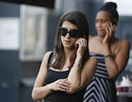 Women use their mobile phones in central London August 30, 2013. REUTERS/Olivia Harris