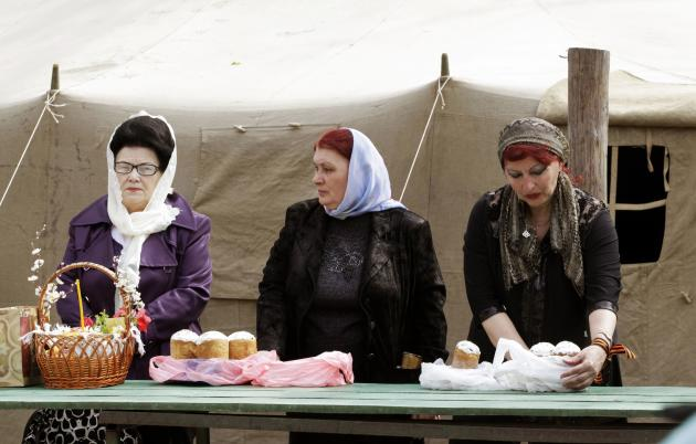 "Orthodox believers wait with ""paskha"" cakes, eggs and other food to be consecrated at the orthodox church ahead of midnight Easter mass in Luhansk"