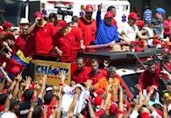 Venezuelan President Hugo Chavez (C) waves to supporters during a campaign rally in Sabaneta, Barinas state. Chavez sang, greeted throngs of supporters and lodged a searing attack on his rival Monday as he stormed into the final stretch of his re-election campaign