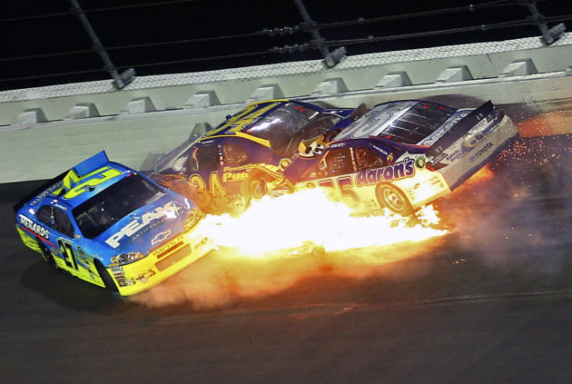 Paul Menard (27), David Ragan (34) and Michael Waltrip (55) wreck coming out of Turn 1 during the NASCAR Budweiser Shootout auto race at Daytona International Speedway, Saturday, Feb. 18, 2012, in Day