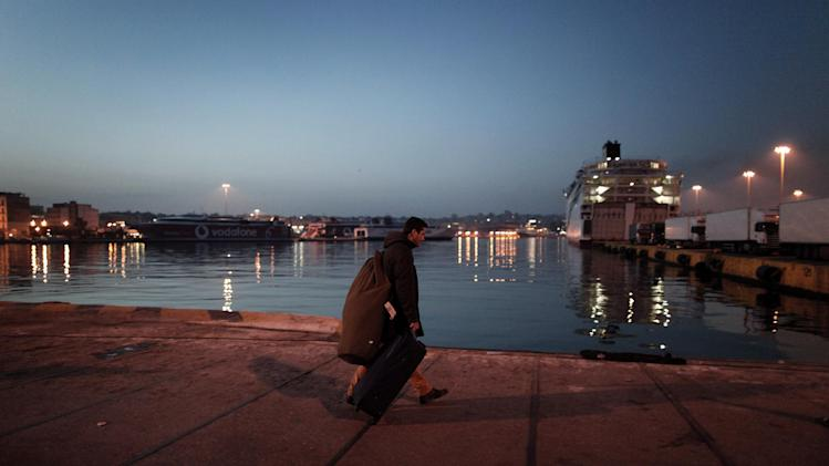 A passenger carries his luggage to his ferry at the Greek capital's port of Piraeus, after striking seamen were forced to return to work early Wednesday, Feb. 6, 2013. Greece's conservative-led government used emergency powers late Tuesday to order the strikers back to work after a six-day walkout to protest pay arrears of over six months, benefit cuts and austerity measures. (AP Photo/Petros Giannakouris)