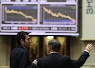 Men look at the IBEX-35 index curve on April 23 at Madrid's stock exchange. European shares dived and the euro hit a 22-month low on Wednesday before an informal EU summit and after the former Greek prime minister warned that Greece might leave the eurozone