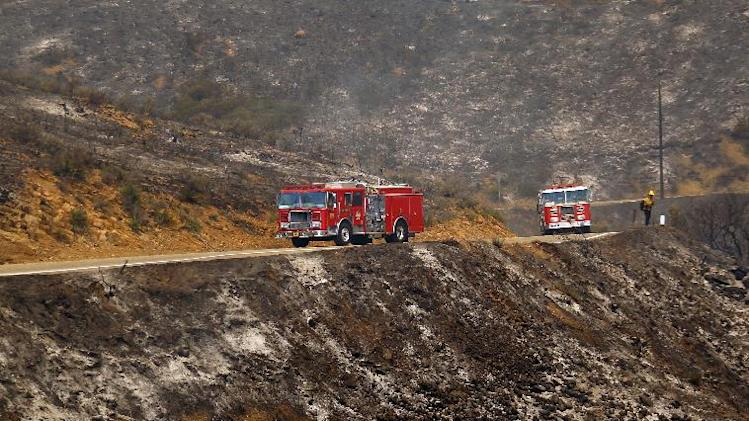 Firefighters keep an eye on a burned hillside in Point Mugu, Calif., Friday, May 3, 2013. A huge wildfire carved a path to the sea and burned on the beach Friday, but firefighters got a break as gusty winds turned into breezes. Temperatures remained high, but humidity levels were expected to soar as cool air moved in from the ocean and the Santa Ana winds retreated. (AP Photo/Nick Ut)