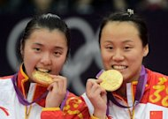 China's Tian Qing (L) and Zhao Yunlei celebrate with their gold medals after beating Japan's Mizuki Fuji and Reika Kakiiwa in the women's doubles badminton final match at the London 2012 Olympic Games in London