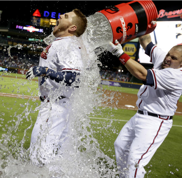 Atlanta Braves' Freddie Freeman, left, is doused with water by Eric Hinske after Freeman hit a home run in the ninth inning as the Braves beat the Marlins 4-3 to clinch at least an NL wild-card playof