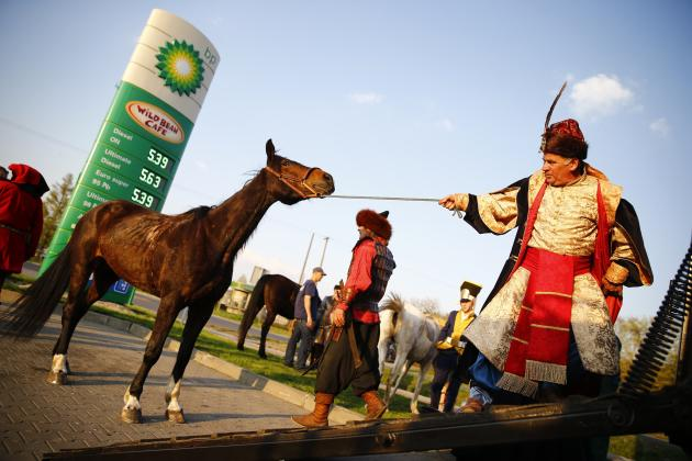 A man dressed in a historic costume pulls a horse during a farewell celebration for a group of pilgrims from the knights brotherhood in Kurzetnik