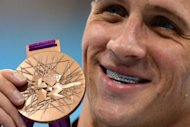 US swimmer Ryan Lochte poses with his bronze medal after the podium ceremony for the men's 200m backstroke swimming event at the London 2012 Olympic Games in London. Lochte's London Olympics ended with a whimper on Thursday as a brutal backstroke-medley double failed to yield gold and he succumbed yet again to old foe Michael Phelps