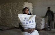 A Palestinian boy holds a sack of flour at a United Nations Relief and Works Agency (UNRWA) aid distribution centre in Gaza City, on April 10, 2013. Israel has answered EU anger over the confiscation of humanitarian aid for Palestinians with accusations diplomats at the scene defied a court order and one struck a policeman