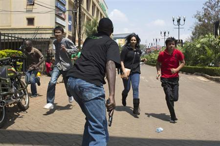 An armed security officer (C) assists civilians escaping from the Westgate Shopping Centre where gunmen went on a shooting spree, in Nairobi September 21, 2013. REUTERS/Siegfried Modola
